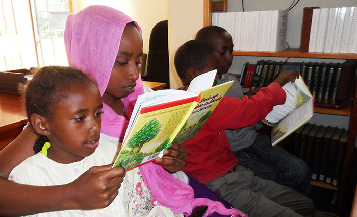 Somalian children reading A Child's Garden of Bible Stories