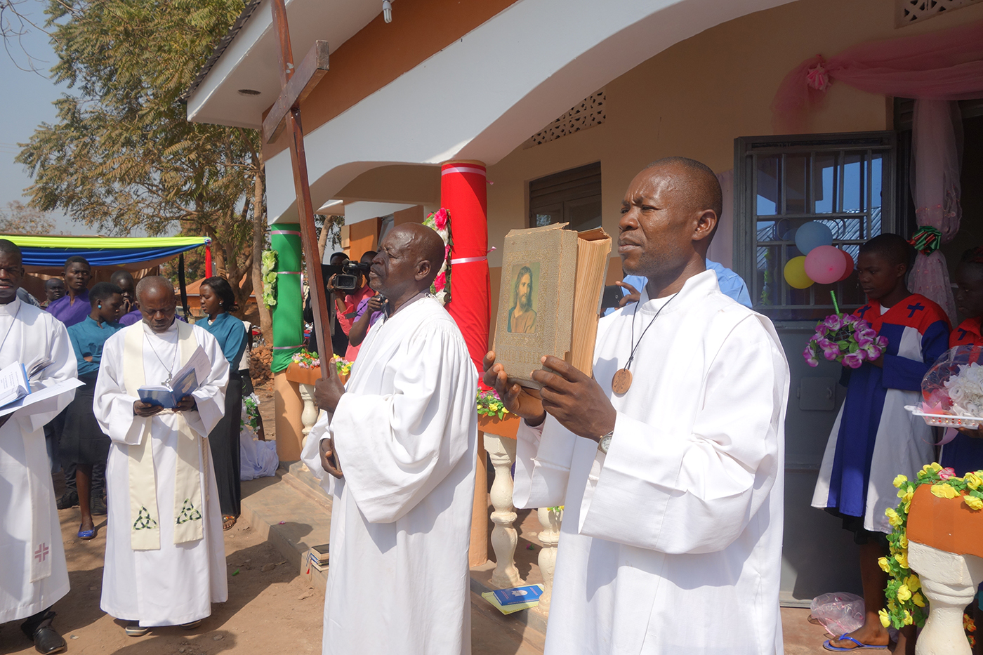 A procession of pastors holding the cross and a Bible