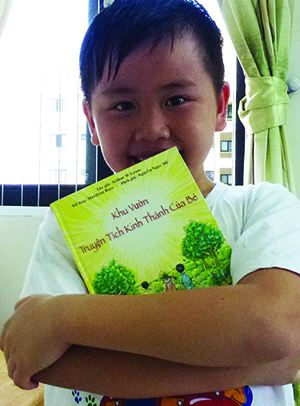 "Danny, a young Lutheran in Vietnam, hugs his copy of the Vietnamese ""A Child's Garden of Bible Stories,"" sponsored by the national LWML."