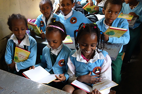 Young Ethiopian girls page through their new Bible storybooks.