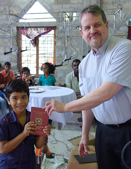Executive director Rev. Matthew Heise distributes LHF's Malayalam-language Small Catechism to families in India.