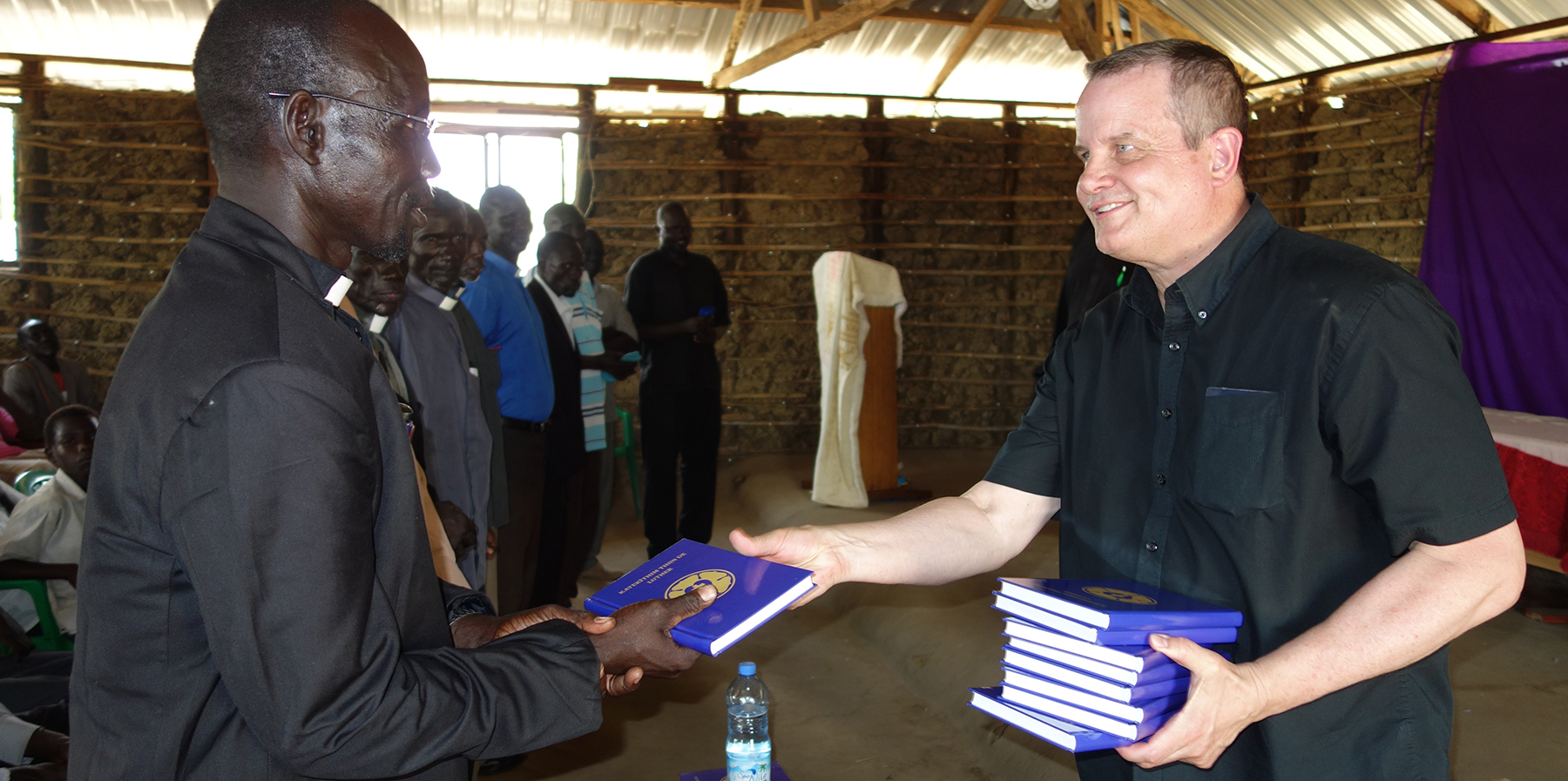 Sudan Heise Distributing Catechism To Pastor